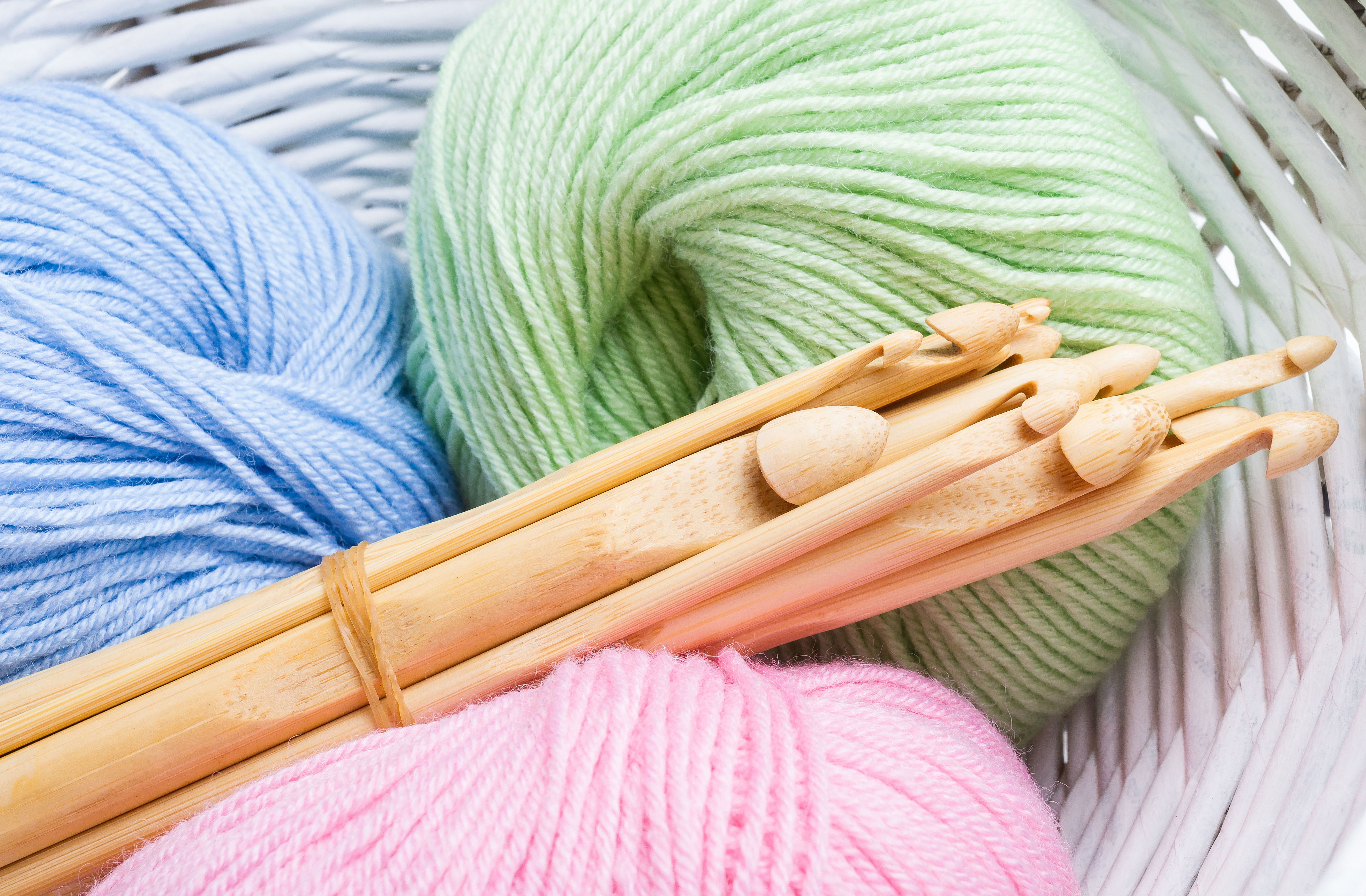 Pastel colored yarn in white basket and wooden crochet hooks of different sizes.